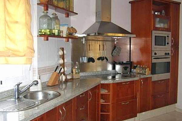 Cocina con muebles de madera y mesa de comer