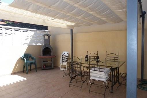 La terraza con barbacoa y un techo solar, flexible