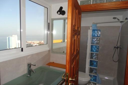 El baño tiene ventanas grandes y vistas despejadas al mar