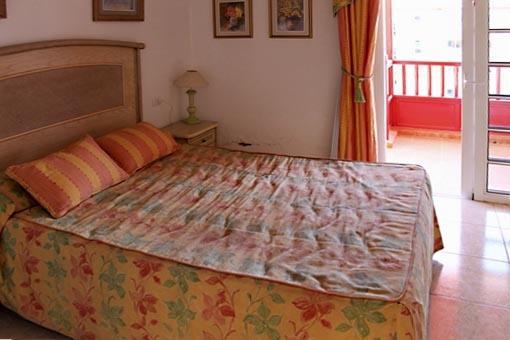 Brillante dormitorio con balcón