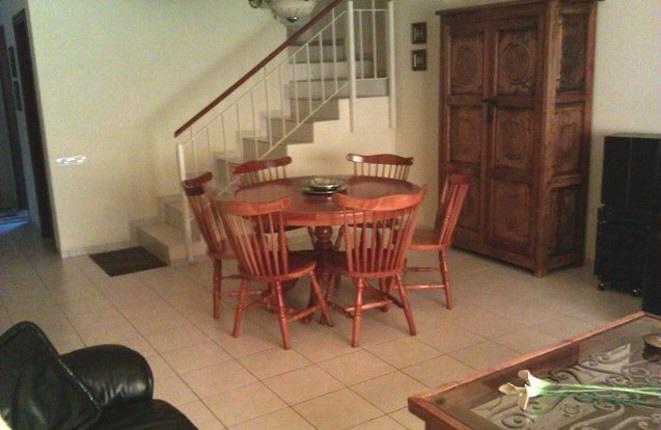 Sala de estar con mesa de comedor y escalera