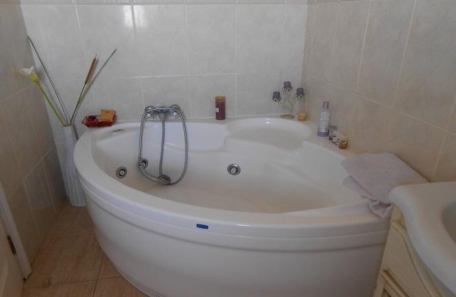 Cuarto de baño con bañera de esquina